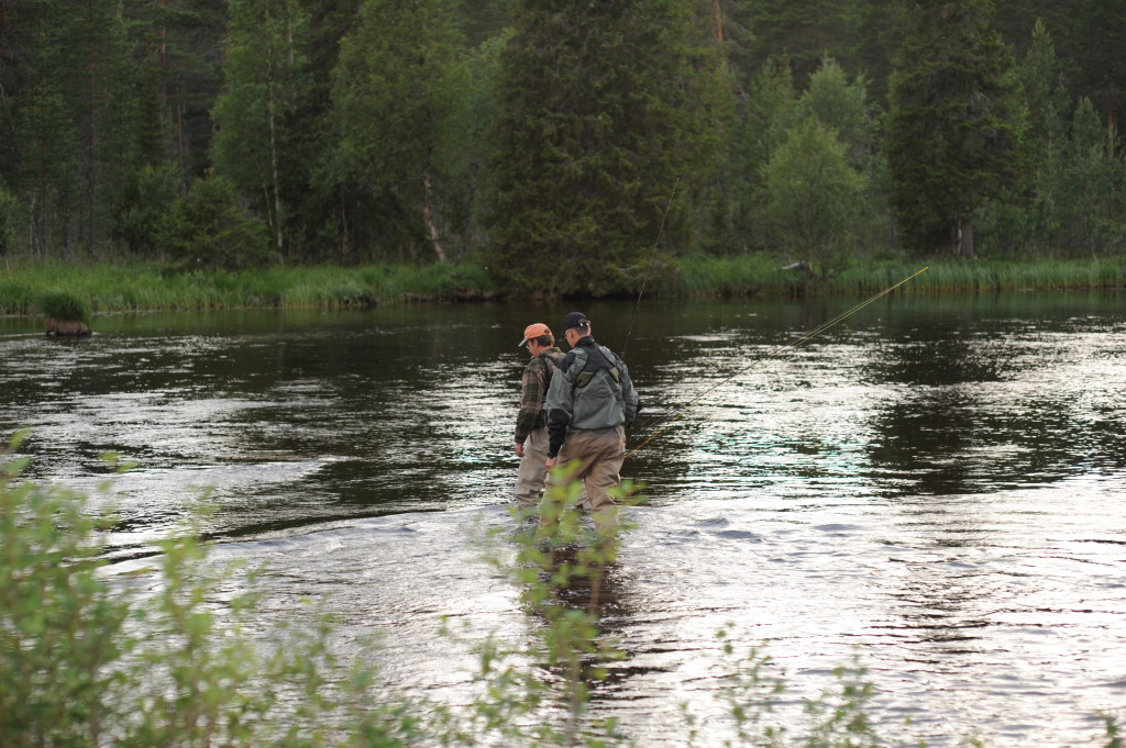 Mosquitoes delight is: two fisherman wading in a stream in the twilightzone