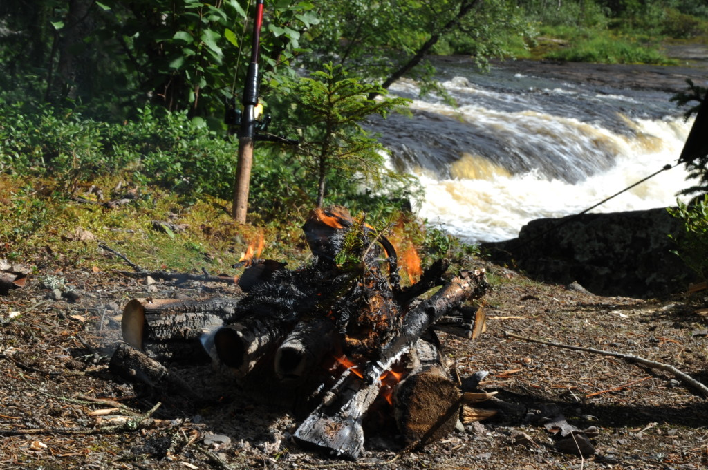 logfire on the banks of a stream with fishing rod