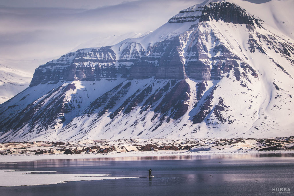 Svalbard sea and mountains, and someone paddling on a board. Image credit Fredrik Granath and Melissa Schaefer.